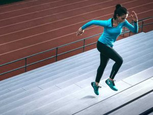Woman training at running track after acupuncture for athletes