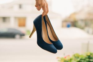 woman holding pair of high heeled shoes