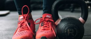 Woman in gym wearing red trainers next to a kettlebell