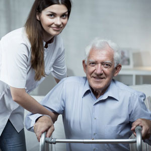 elderly man with zimmer frame having home visit from physiotherapist